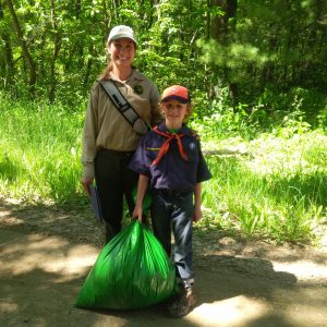 Bradlee Gehlhoff, a second-grader at St. Paul Lutheran School in Stevensville, shows off the bag filled with invasive garlic mustard plants he'd plucked at Grand Mere State Park this summer. The DNR's Heidi Frei, left, said volunteers are a huge help in keeping invasive species under control. Photo Credit: Mary Gehlhoff
