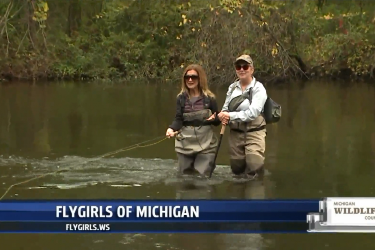 Two women standing next to each other, one is fly fishing