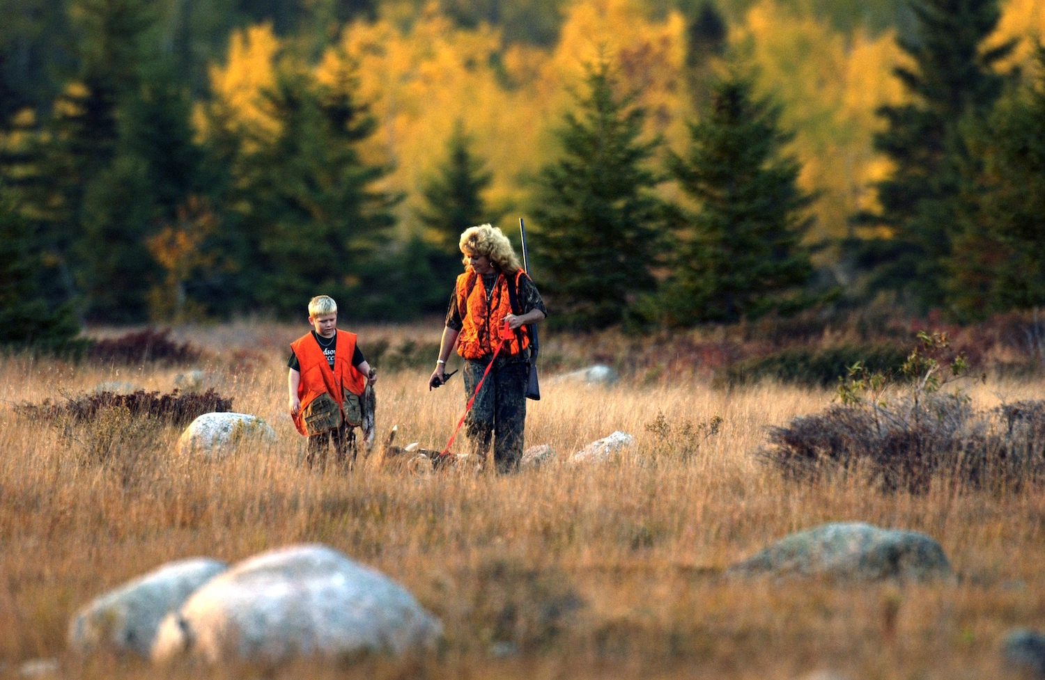 Mother and son stand in field while upland game hunting