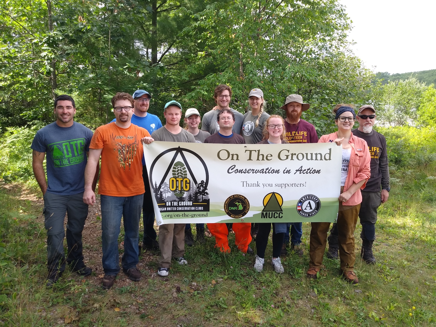 "Volunteers gather for a picture, holding a sign that says ""On the Ground"""