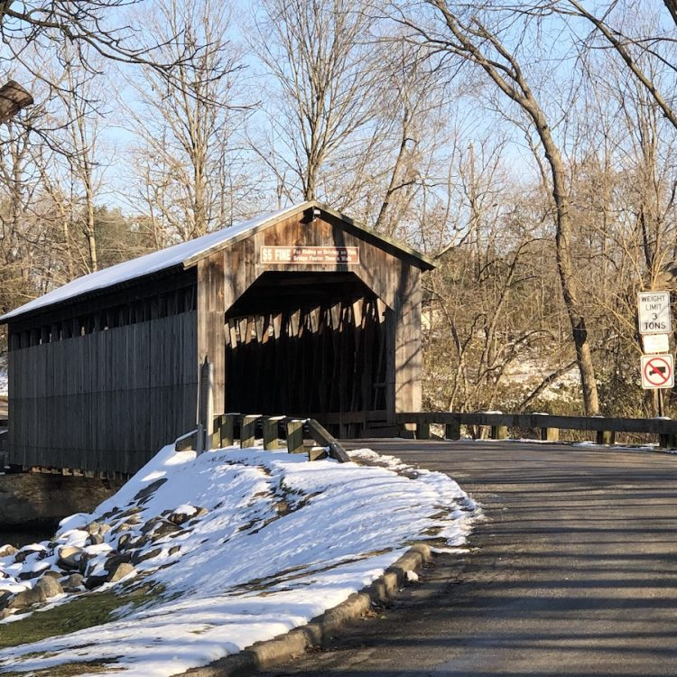 A wooden covered bridge over a road