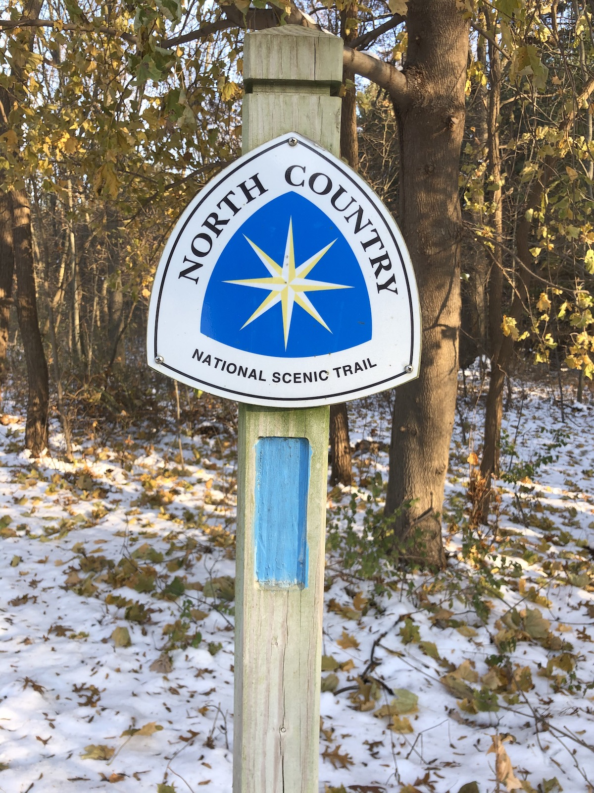 A blue and white sign identifying the North Country Trail