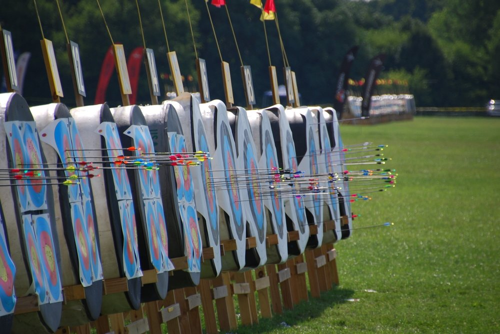Side-view of a dozen archery targets sitting on grass