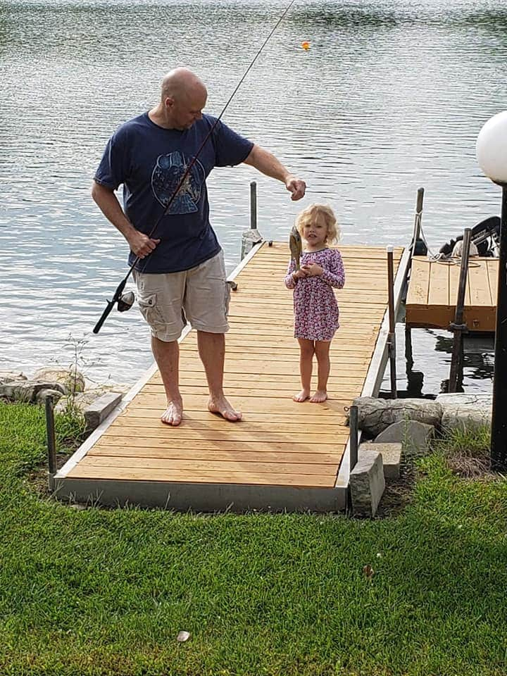 Father and daughter show fish they caught