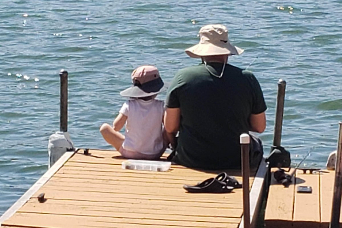 Father and daughter fishing off a dock