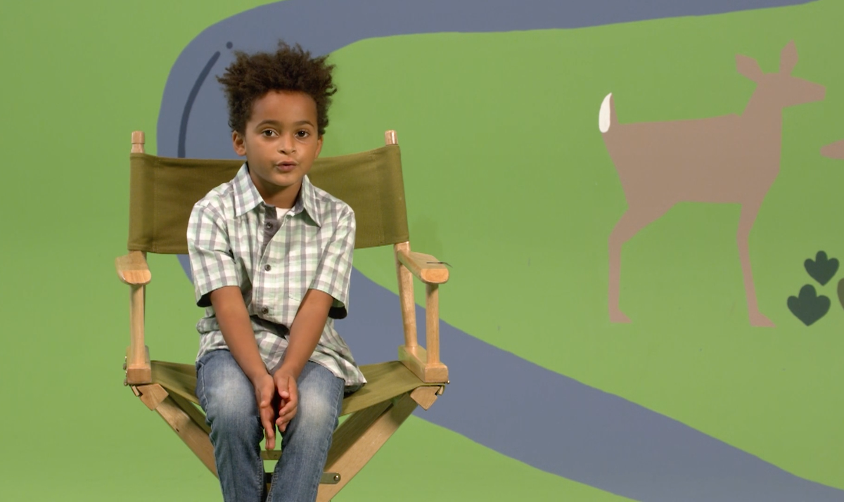 Young boy sitting on a chair in front of a mural