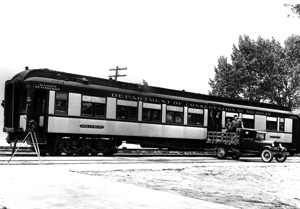 "Black and white image of train car with label ""Department of Conservation of Michigan"""